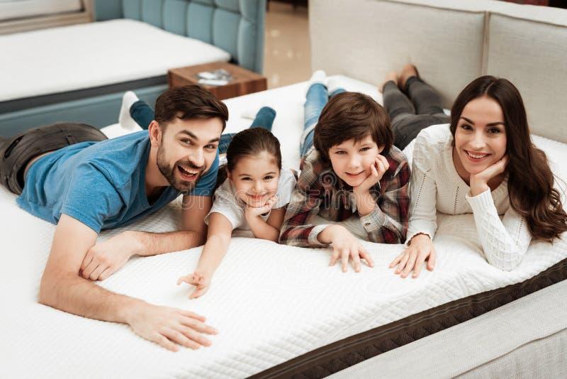 De gelukkige familie ontspant op matras in orthopedische meubilairopslag De grote zachtheid van de familiecontrole van matras royalty-vrije stock foto's