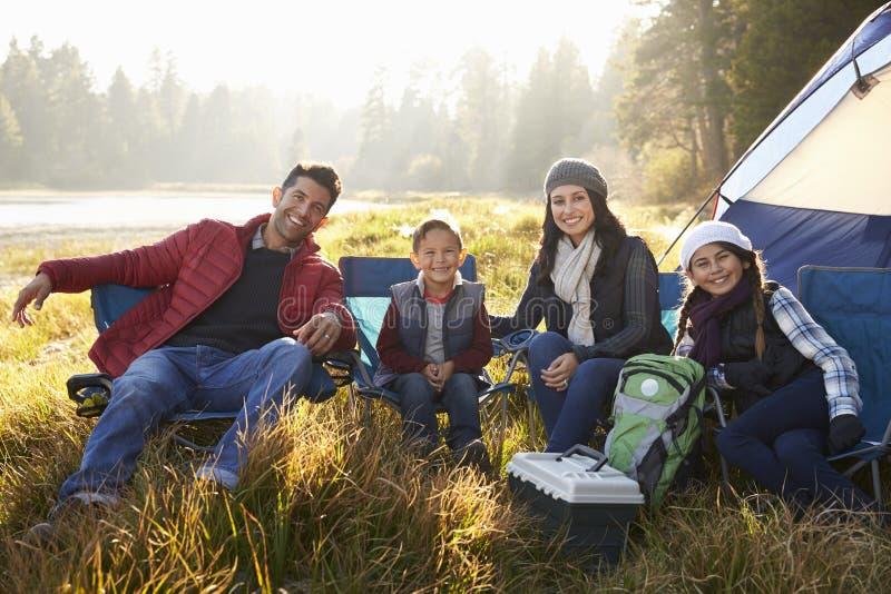De gelukkige familie op een het kamperen reis zit door tent kijkend aan camera stock foto