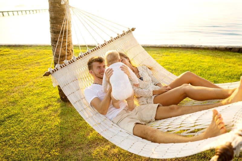 De gelukkige familie op een tropisch eiland bij zonsondergang ligt in een hangmat en speelt met hun zoon stock afbeeldingen