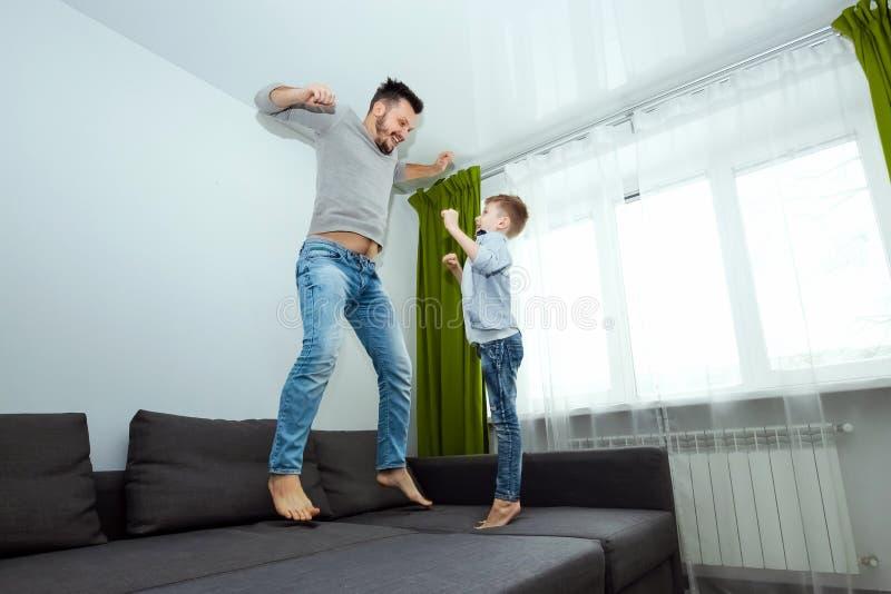 De gelukkige familie, de Papa en de zoon brengen tijd die samen, rond aan het bed door, die met hoofdkussens slaan voor de gek ho royalty-vrije stock foto's