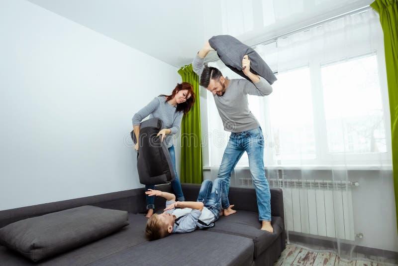 De gelukkige familie, de Papa, het Mamma en de zoon brengen tijd die samen, rond aan het bed door, die met hoofdkussens slaan voo royalty-vrije stock fotografie