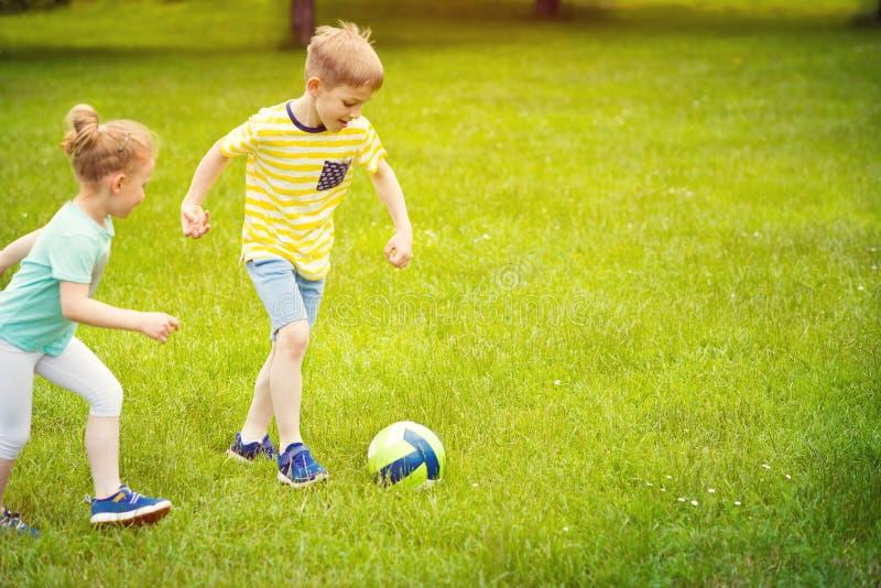 De gelukkige familie speelt voetbal in zonnig park royalty-vrije stock foto