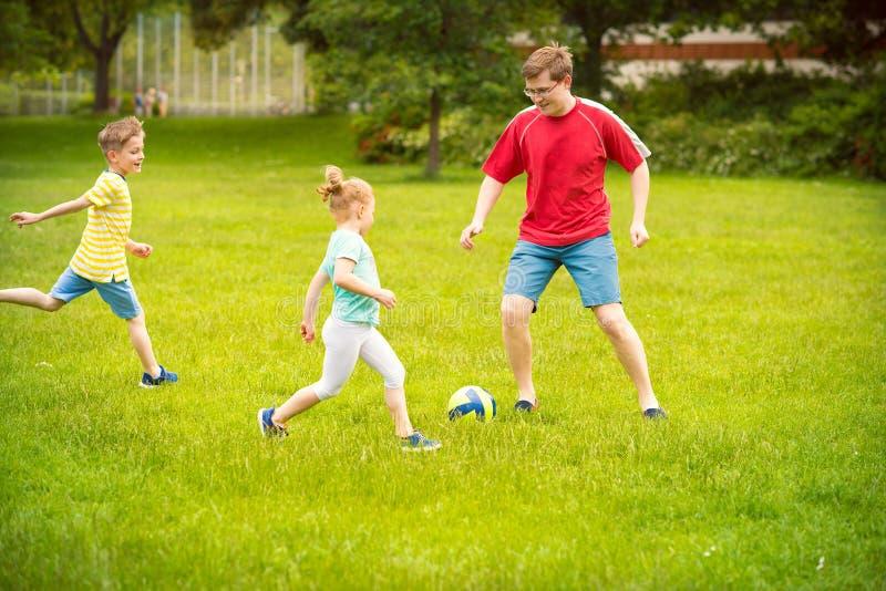 De gelukkige familie speelt voetbal in zonnig park royalty-vrije stock afbeelding