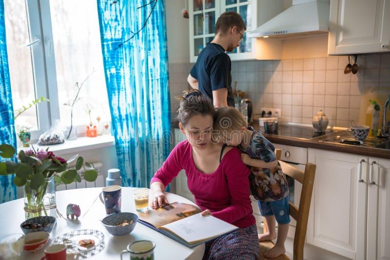De gelukkige familie thuis keuken las samen boek met peuterjongen stock foto