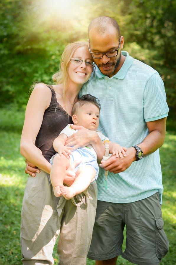 De gelukkige familie tussen verschillende rassen geniet van een dag in het park met adop stock afbeelding