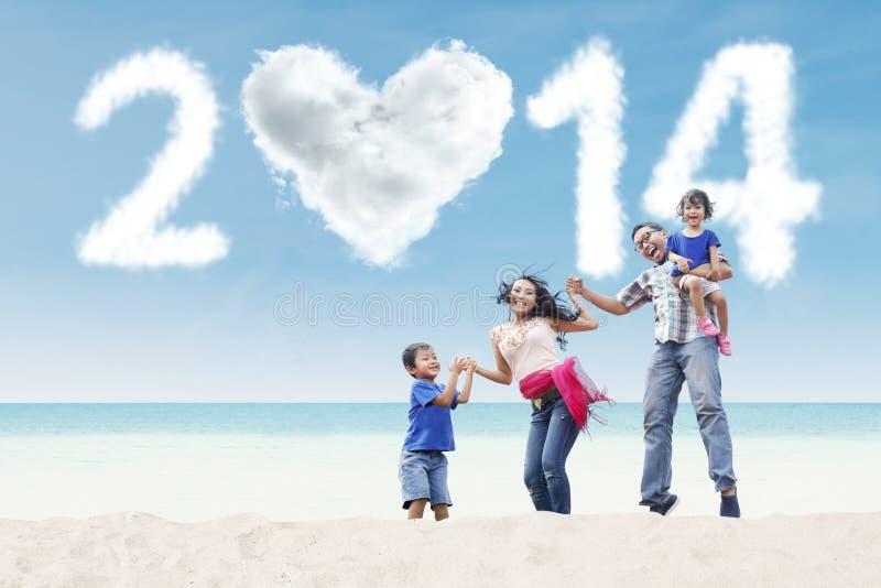 De gelukkige familie viert nieuw jaar bij strand stock foto's
