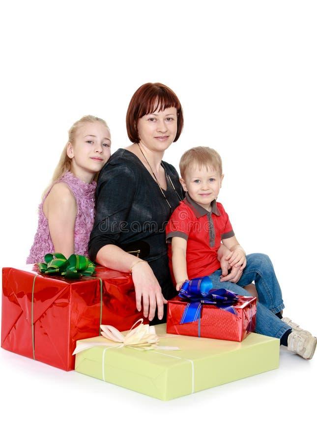 De gelukkige familie zit omringd door giftenmoeder royalty-vrije stock foto