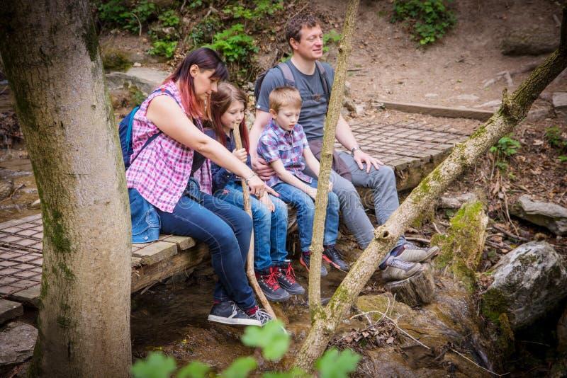 De gelukkige familie zit op een houten brug in het midden van bos royalty-vrije stock fotografie