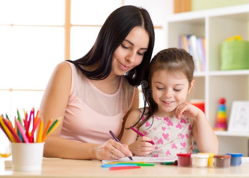 De gelukkige familiemoeder en de jong geitjedochter schilderen samen De vrouw helpt kindmeisje royalty-vrije stock afbeelding