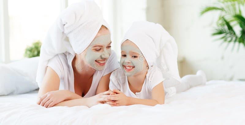 De gelukkige familiemoeder en de kinddochter maken het masker van de gezichtshuid stock afbeeldingen