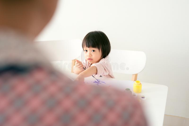 De gelukkige de familiemoeder en dochter schilderen samen De Aziatische vrouw helpt haar kindmeisje stock afbeeldingen