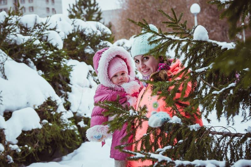 De gelukkige familiemoeder en dochter van het babymeisje in de winter in openlucht stock foto's