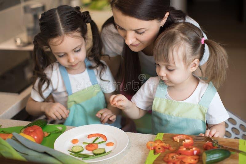 De gelukkige de familiemoeder en jonge geitjes bereiden gezond voedsel voor, improviseren zij samen in de keuken stock afbeeldingen