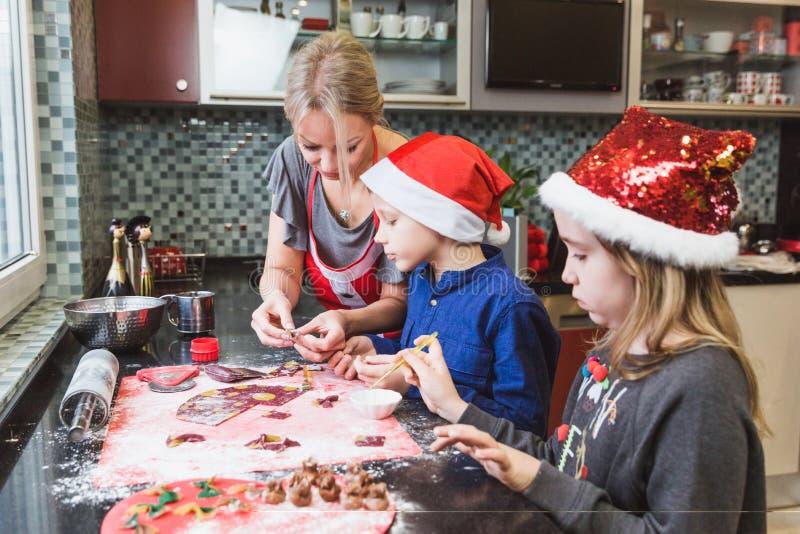 De gelukkige familiemoeder en de de kinderenzoon en dochter bakken deegwaren voor Kerstmis royalty-vrije stock afbeeldingen