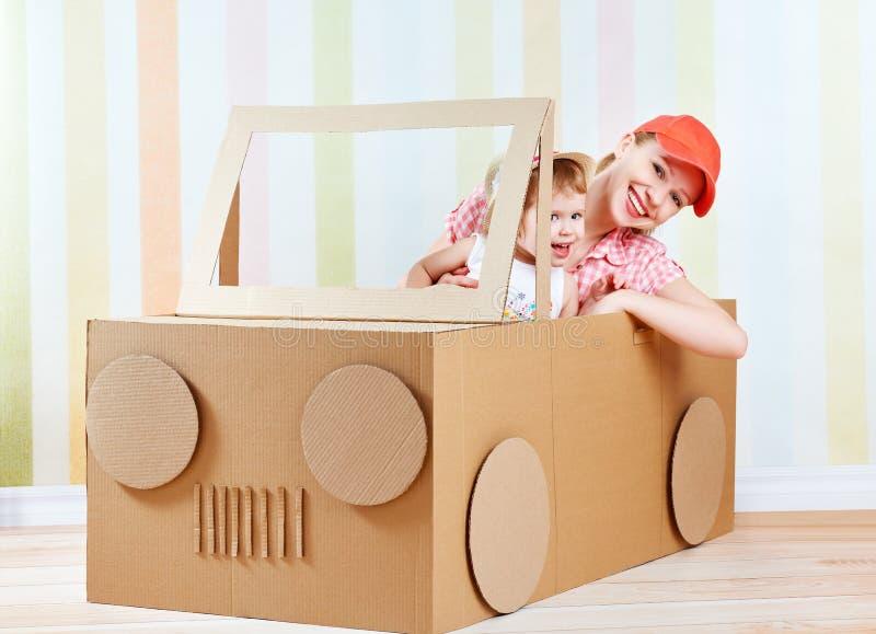 De gelukkige familiemoeder en weinig die dochter berijden op stuk speelgoed auto van karton wordt gemaakt royalty-vrije stock foto