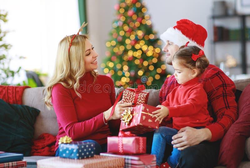 De gelukkige familieouders en open kind de dochter stellen op Kerstmisochtend voor royalty-vrije stock foto