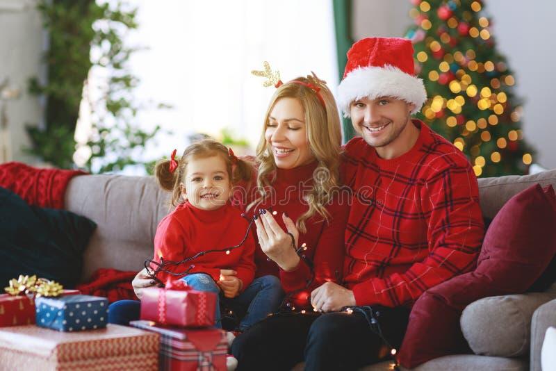 De gelukkige familieouders en open kind de dochter stellen op Kerstmisochtend voor stock afbeelding