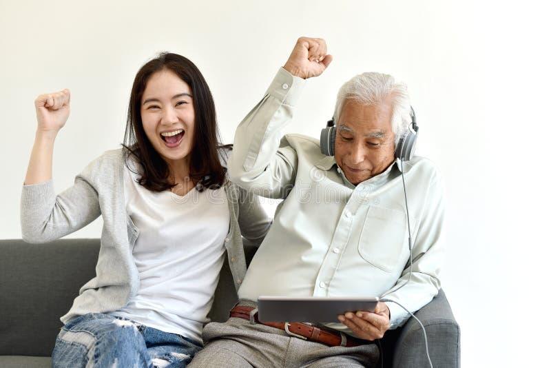 De gelukkige familietijd, de Glimlachende Aziatische dochter en de bejaarde vader genieten van samen lettend op film van laptop c stock fotografie