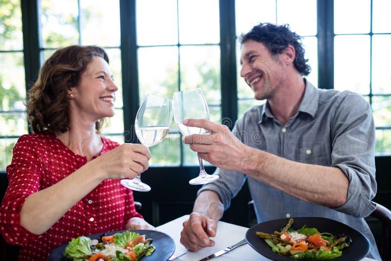 De gelukkige fluiten op middelbare leeftijd van de paar roosterende champagne terwijl het hebben van lunch stock afbeeldingen