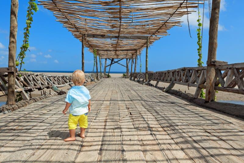 De gelukkige gang van de babyjongen door houten brug aan oceaanstrand stock foto