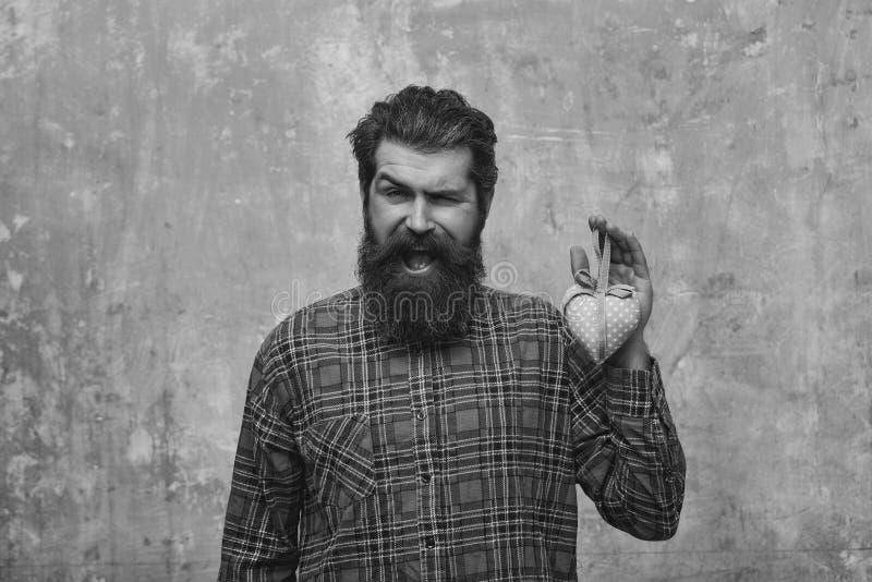 De gelukkige gebaarde mens met baard houdt rooskleurig textielhart stock fotografie