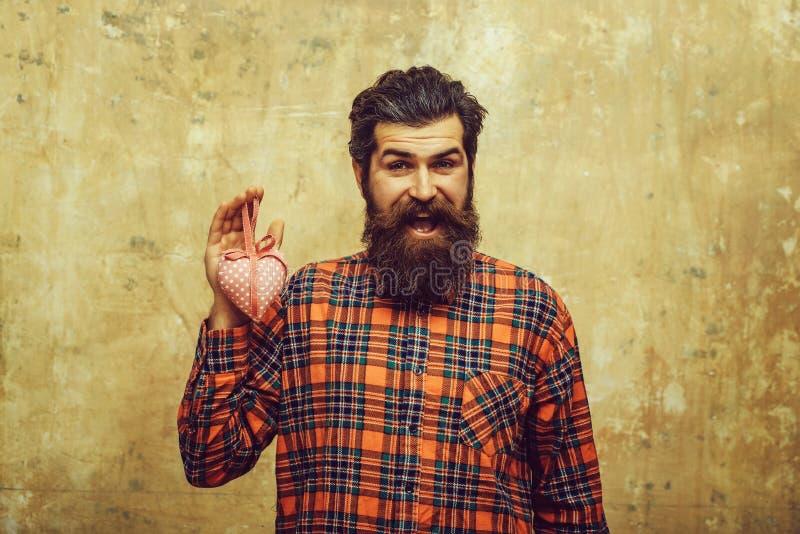 De gelukkige gebaarde mens met baard houdt rooskleurig textielhart royalty-vrije stock afbeelding