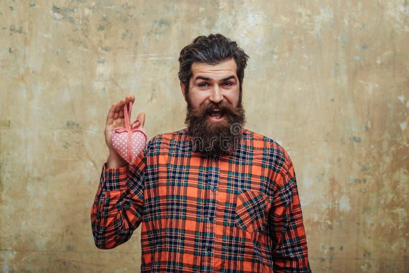 De gelukkige gebaarde mens met baard houdt rooskleurig textielhart stock foto's