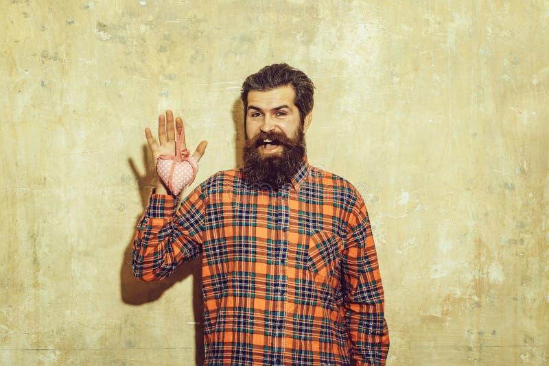 De gelukkige gebaarde mens met baard houdt rooskleurig textielhart royalty-vrije stock foto
