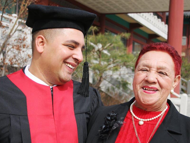 De gelukkige gediplomeerde deelt een ogenblik met zijn grootmoeder stock foto's