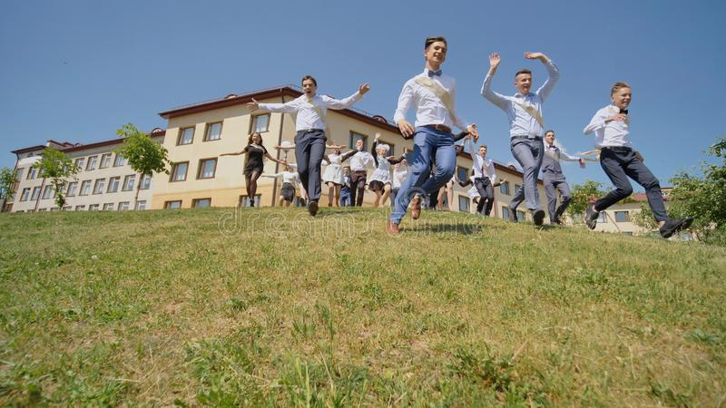 De gelukkige gediplomeerden van de Russische school verschijnen van achter de heuvel en lopen naar geluk stock foto