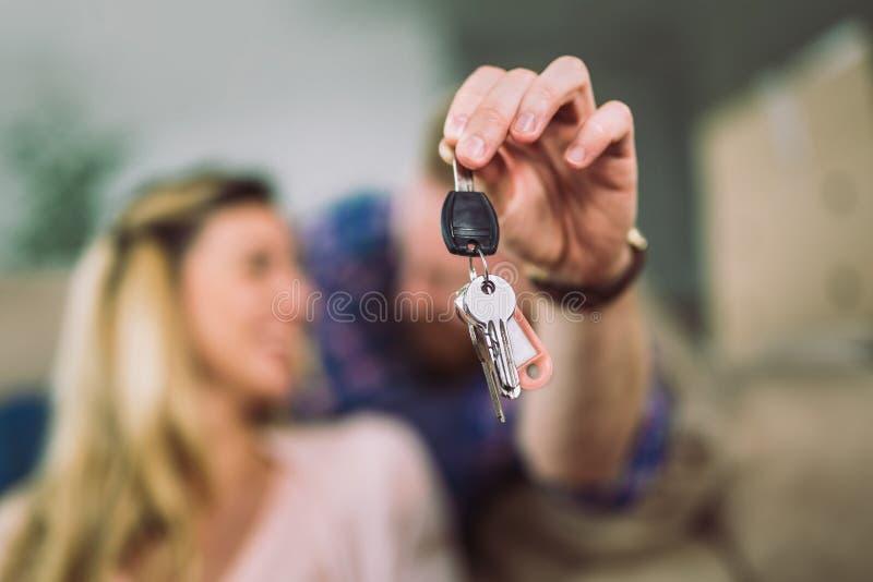 De gelukkige gehuwde mensen kopen nieuwe flat Paar die sleutels tonen aan nieuw huis stock foto