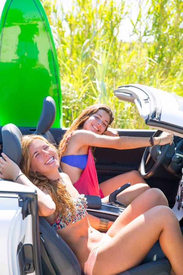 De gelukkige gekke meisjes die van de tienersurfer op auto glimlachen stock afbeeldingen