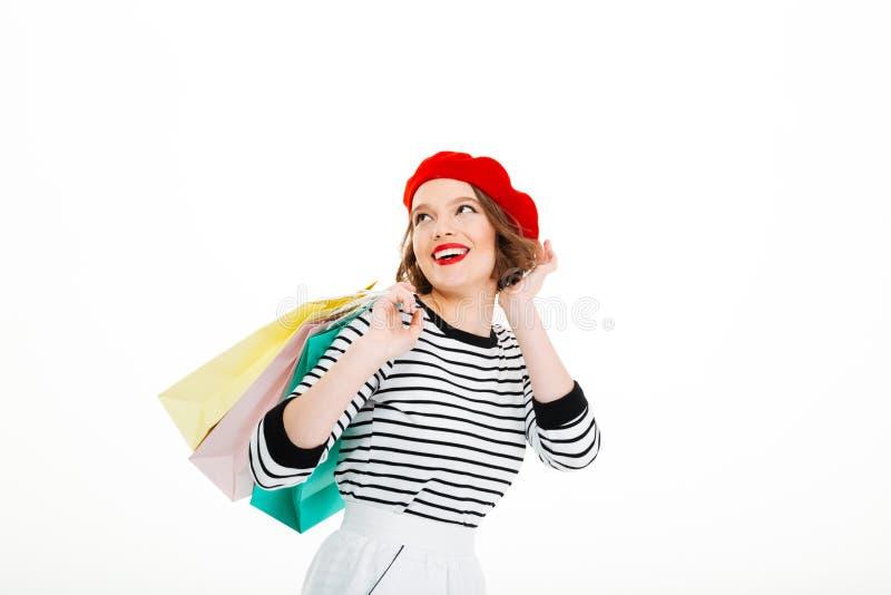 De gelukkige gembervrouw met pakketten verbetert kapsel en weg het kijken stock foto's