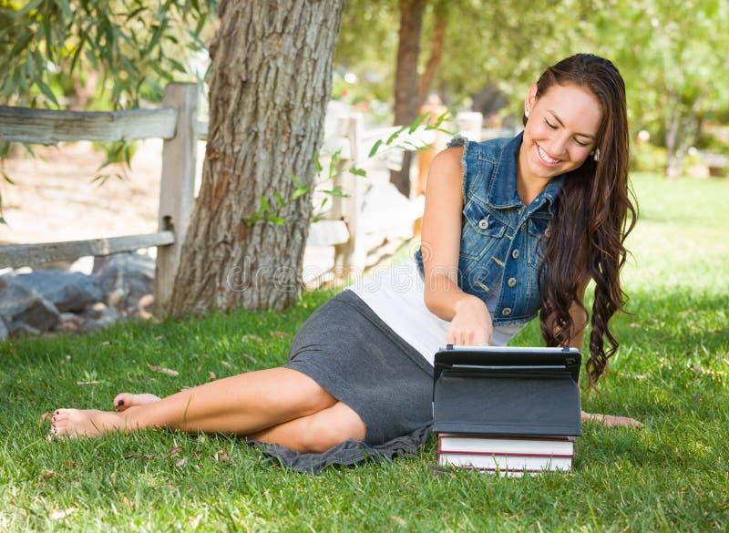 De gelukkige Gemengde Computer van de Studentenwith books using van de Rastiener Vrouwelijke stock afbeeldingen