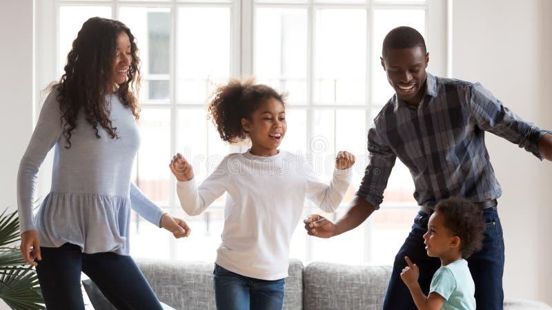 De gelukkige gemengde rasfamilie heeft pret thuis samen dansend stock fotografie