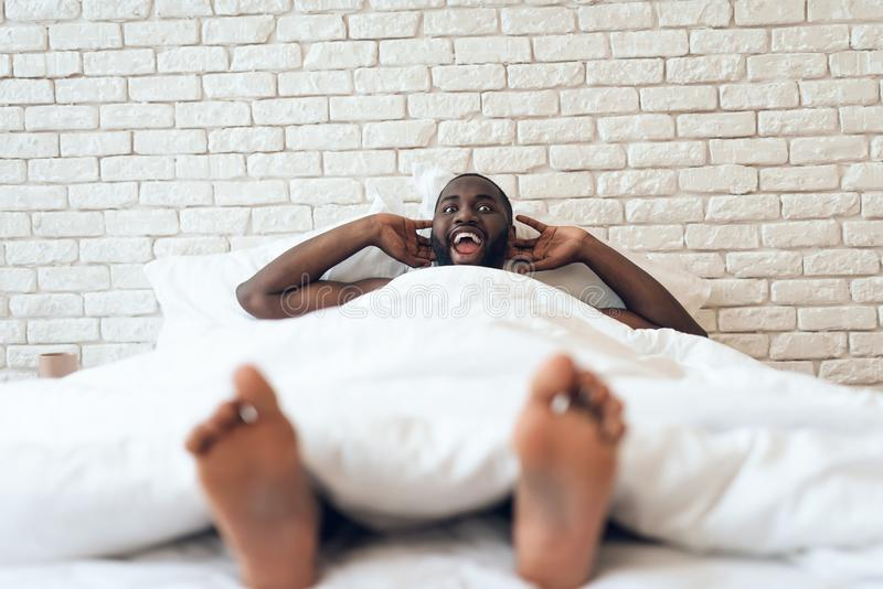 De gelukkige gewekte mens wordt uitgerekt uit in bed stock foto's
