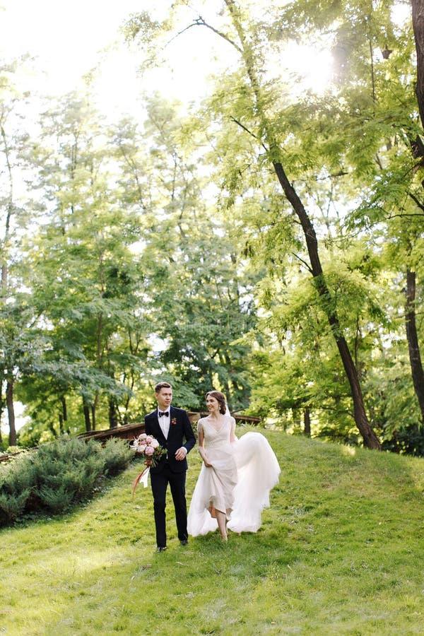 De gelukkige de glimlachbruid en bruidegom bekijken elkaar en lopend in de groene tuin Huwelijk in de zomer in het park gelukkig stock afbeeldingen