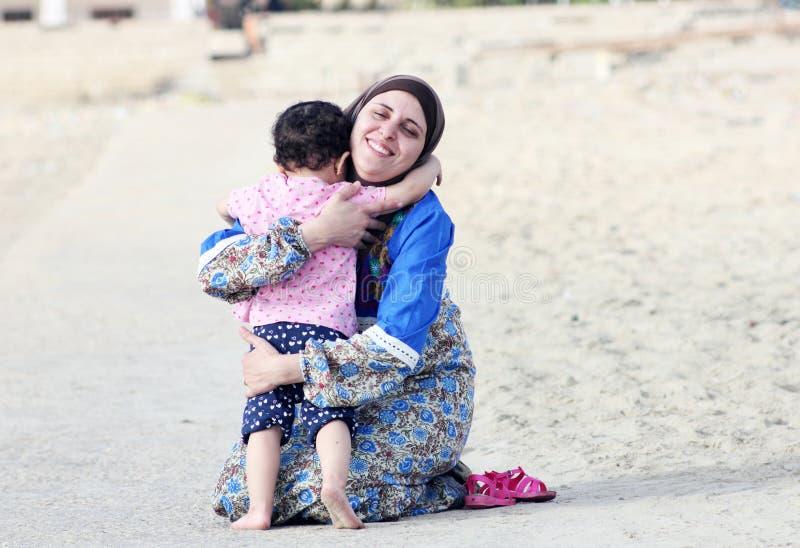 De gelukkige glimlachende Arabische moslimmoeder koestert haar babymeisje stock foto's