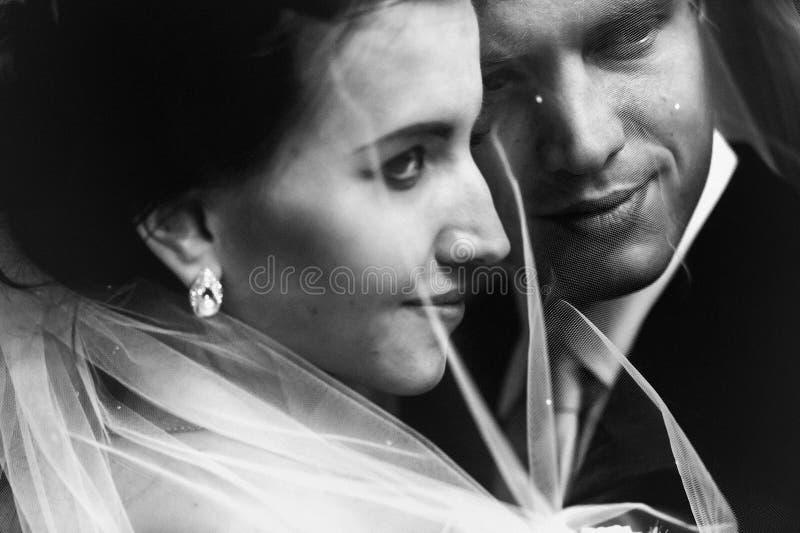 De gelukkige glimlachende bruid van het jonggehuwdepaar en knappe bruidegom onder vei stock afbeeldingen