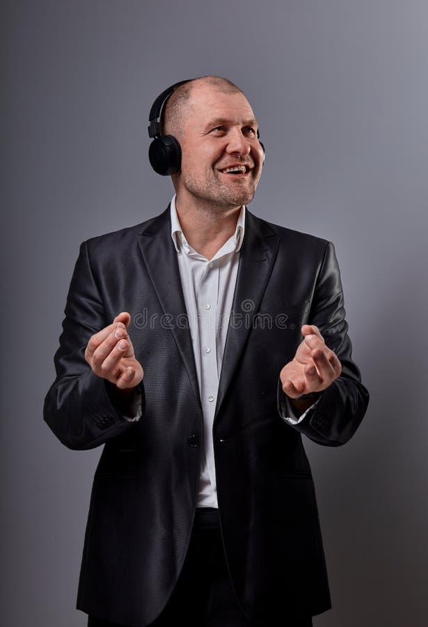 De gelukkige glimlachende dansende kale mens die de muziek in draadloze hoofdtelefoon en de handen tonen zen ondertekent en met h stock afbeelding