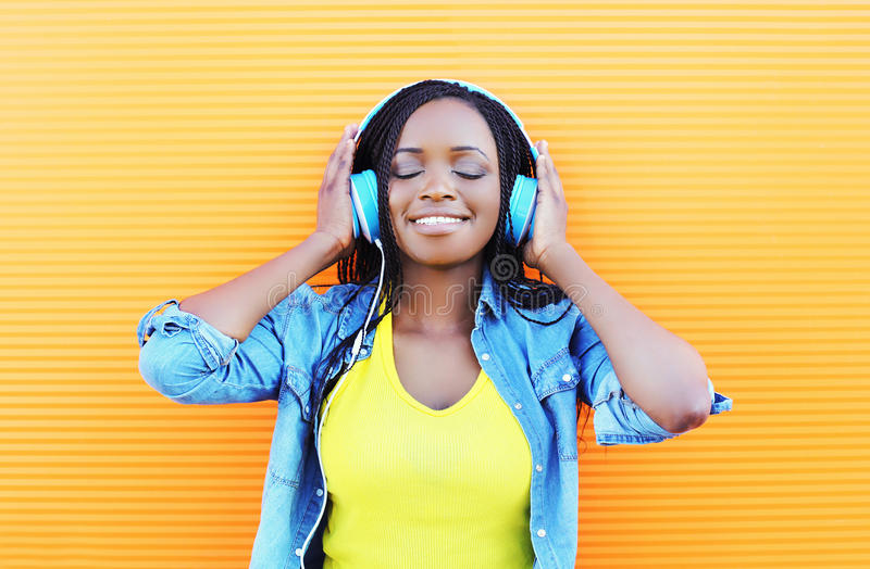 De gelukkige glimlachende jonge Afrikaanse vrouw met hoofdtelefoons het genieten van luistert aan muziek royalty-vrije stock afbeeldingen