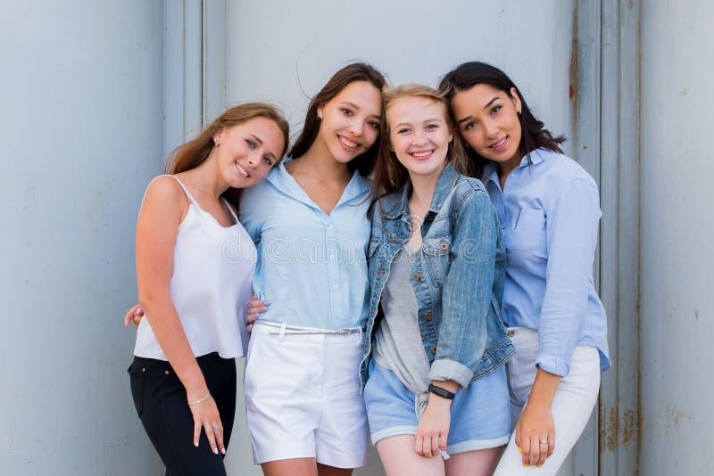 De gelukkige glimlachende jonge meisjes lachen en bekijken de camera stock foto