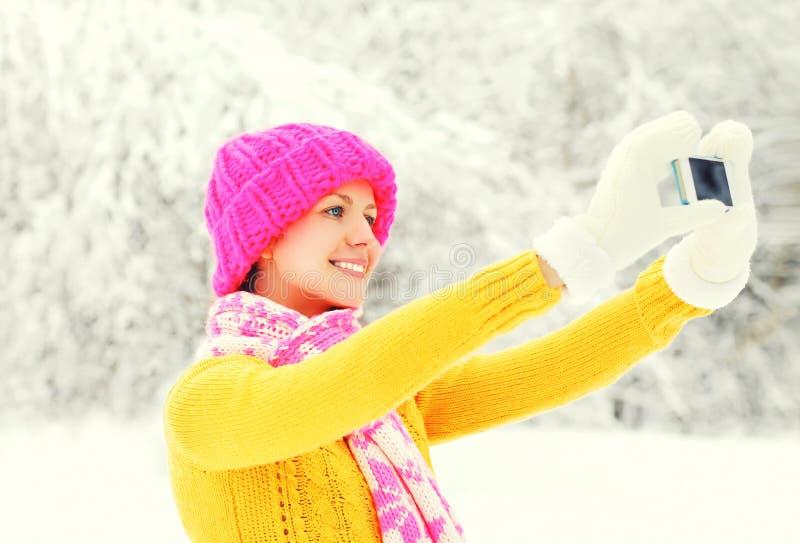 De gelukkige glimlachende jonge vrouw die van de manierwinter beeld zelfportret op smartphone over sneeuwbomen nemen die kleurrij royalty-vrije stock afbeeldingen