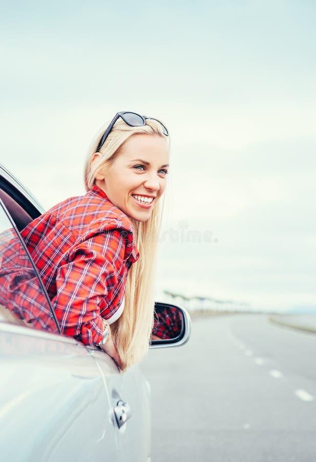 De gelukkige glimlachende jonge vrouw kijkt uit van autoraam royalty-vrije stock foto