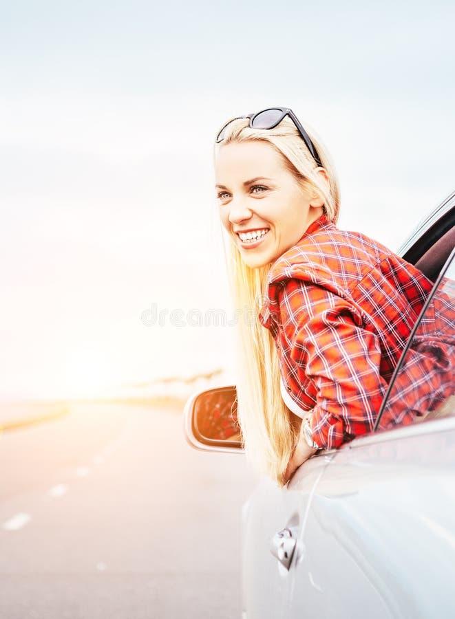 De gelukkige glimlachende jonge vrouw kijkt uit van autoraam stock foto