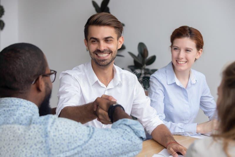 De gelukkige glimlachende Kaukasische mannelijke collega van Afrikaans-Amerikaan van de manager schuddende hand royalty-vrije stock foto's