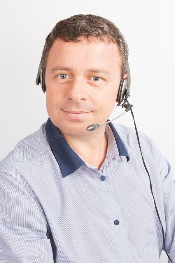 de gelukkige glimlachende mannelijke exploitant van de klantenondersteuningstelefoon op het werk royalty-vrije stock afbeeldingen