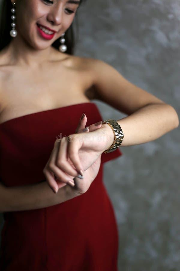 De gelukkige glimlachende mooie jonge sexy vrouw in rode partijkleding kijkt royalty-vrije stock fotografie