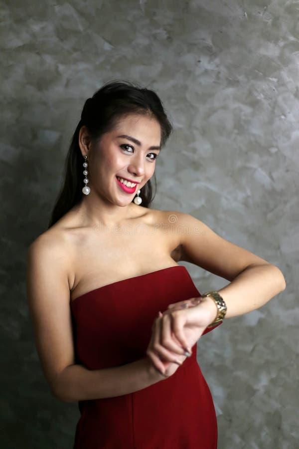 De gelukkige glimlachende mooie jonge sexy vrouw in rode partijkleding kijkt stock afbeeldingen