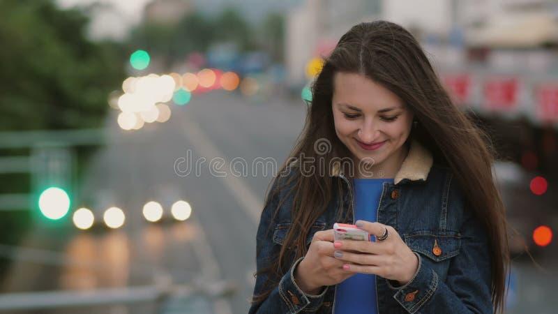 De gelukkige, glimlachende mooie vrouw gebruikt een smartphone zich bevindt op de brug De wind blaast haar haar 4K royalty-vrije stock afbeeldingen